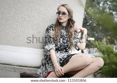 Beautiful woman in glasses sitting at column