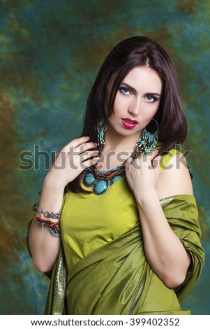 Beautiful woman in green indian sari and jewelry on colorful background - stock photo