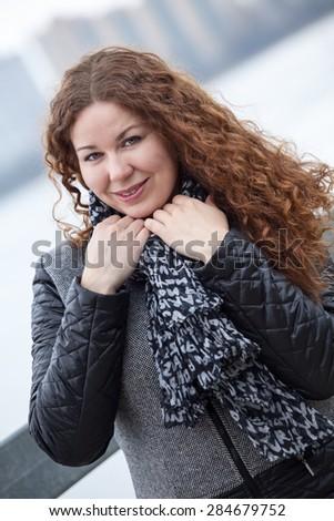 Beautiful woman in grey coat portrait, long curly hair, outdoors - stock photo