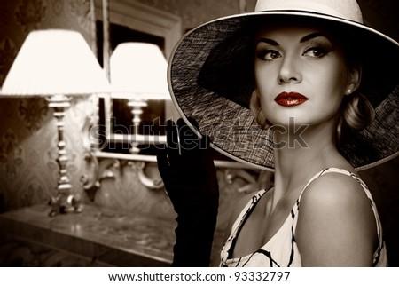Beautiful woman in hat in luxury interior. - stock photo