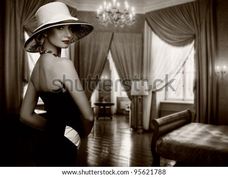 Beautiful woman in hat in luxury room. - stock photo