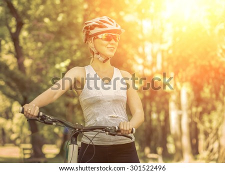 Beautiful woman in helmet and glasses stay on the bicycle. - stock photo