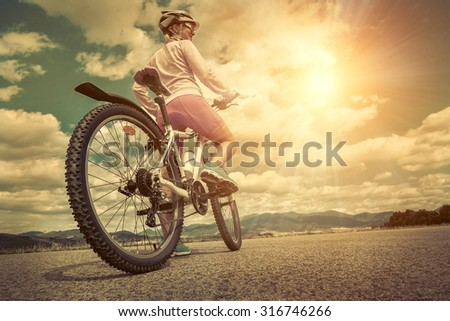Beautiful woman in helmet and glasses stay on the bicycle under sky with clouds. - stock photo