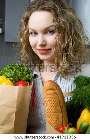Beautiful woman in kitchen with vegetables - stock photo