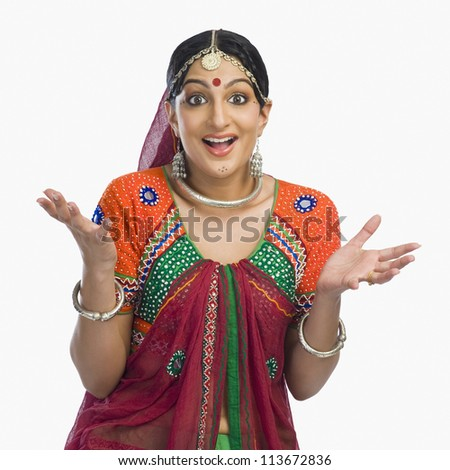 Beautiful woman in lehenga choli shrugging - stock photo