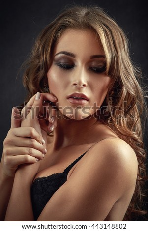 beautiful woman in lingerie on black background, toned image