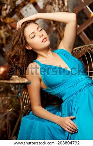 Beautiful woman in long blue dress. Young girl in luxury fashionable dress - stock photo