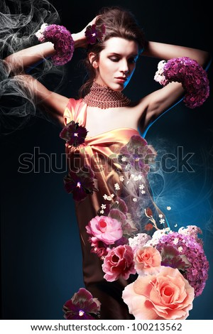 beautiful woman in long dress in blue light with flowers - stock photo