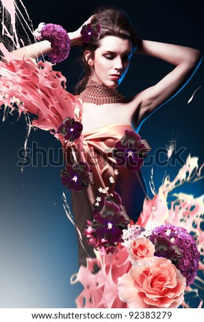 beautiful woman in long dress in blue light with flowers and splash - stock photo