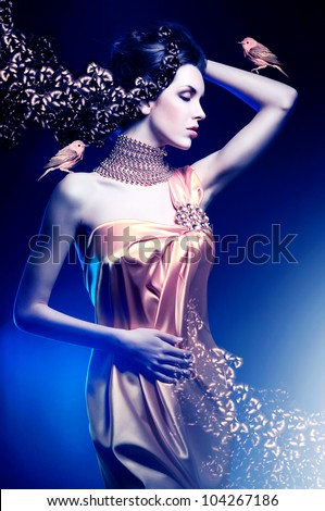beautiful woman in long dress with jewelry and birds - stock photo