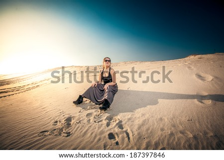 Beautiful woman in long skirt sitting on sand dune against blue sky and sun