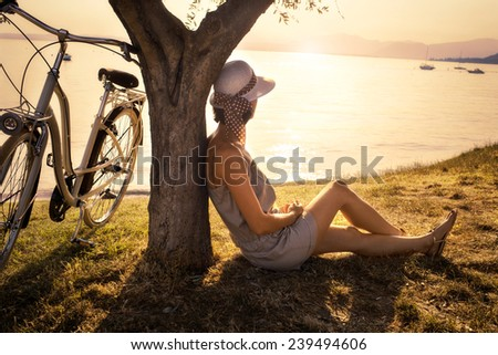 Beautiful woman in love waiting under an olive tree's at sunset with lake view - stock photo