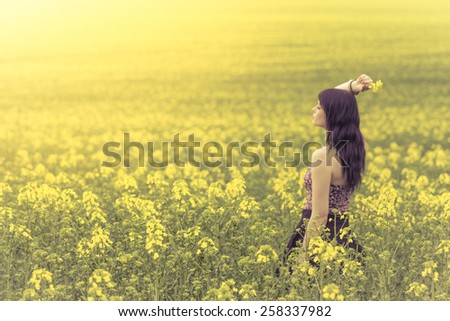 Beautiful woman in meadow of yellow flowers from side behind. Attractive genuine young girl enjoying the warm summer sun in a wide green and yellow meadow. Part of series. - stock photo
