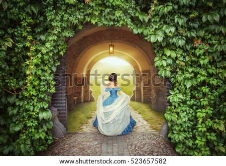 Beautiful woman in medieval dress on the mysterious sunny road