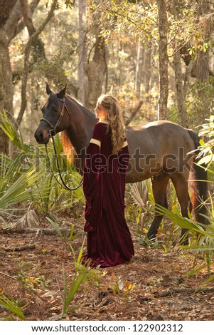 beautiful woman in medieval dress with horse in forest - stock photo