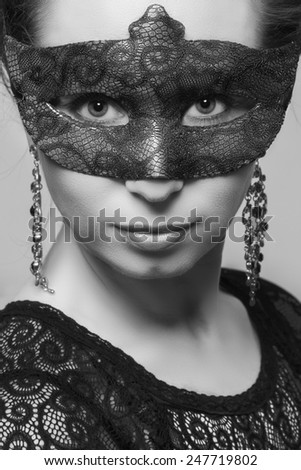 Beautiful woman in mysterious mask, black and white - stock photo