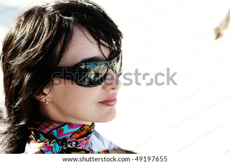 Beautiful woman in neckerchief and sunglasses relaxing under the sun - stock photo