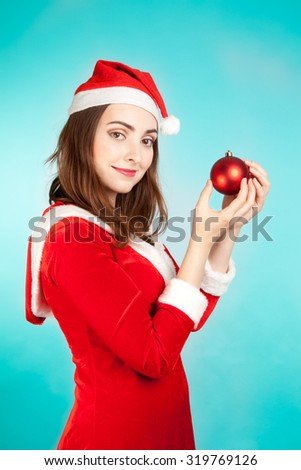 Beautiful woman in new year costume holding red ball - stock photo