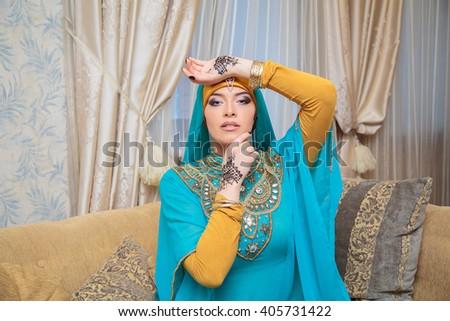 beautiful woman in oriental style with mehendi in hijab - stock photo