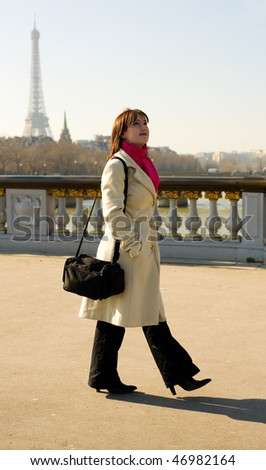 Beautiful woman in Paris walking on the Pont Alexandre III - stock photo