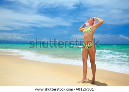 Beautiful woman in pink hat on the beach.
