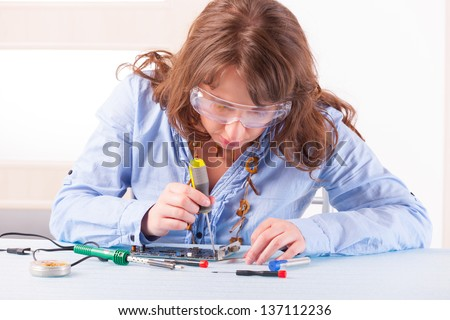 Beautiful woman in protective glasses fixing computer parts with screwdriver and soldering iron - stock photo