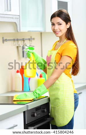 Beautiful woman in protective gloves cleaning electric range with rag and spray - stock photo