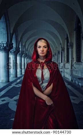 Beautiful woman in red cloak outdoor - stock photo