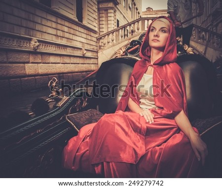 Beautiful woman in red cloak riding on gondola - stock photo
