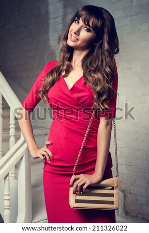 Beautiful woman in red dress holding handbag standing on stairs against white brick wall  - stock photo