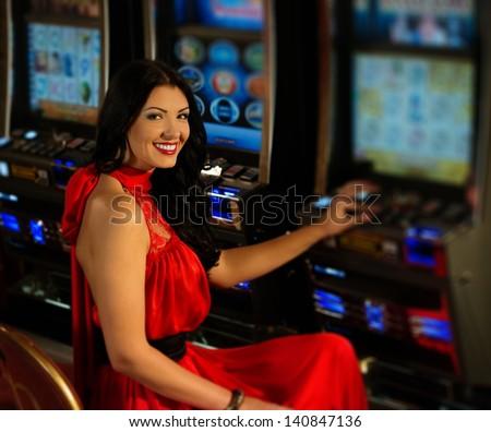 Beautiful woman in red dress playing slot machine - stock photo