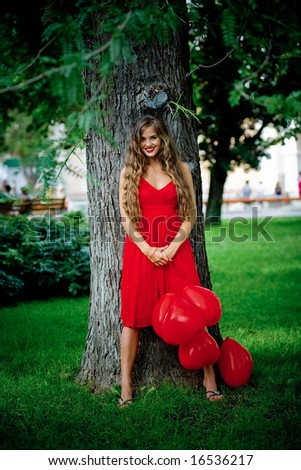 Beautiful woman in red dress staying near tree holding bunch of balloons-hearts and smiling - stock photo