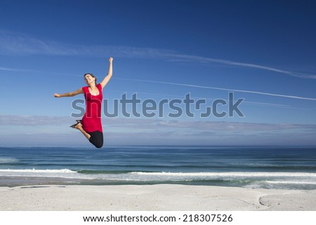Beautiful woman in red jumping with a beautiful beach in the back - stock photo