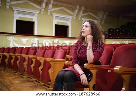 Beautiful woman in red sit in empty auditorium and looks at stage  - stock photo