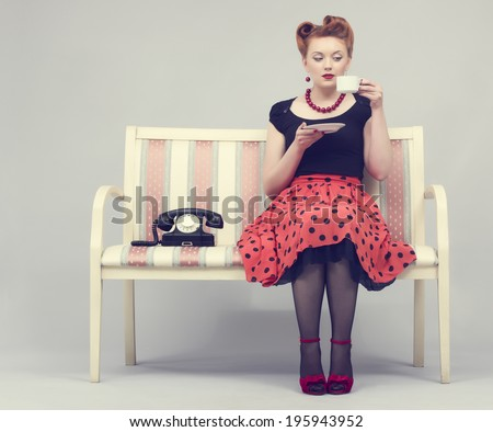 Beautiful woman in retro style drinks coffee sitting on the couch. - stock photo