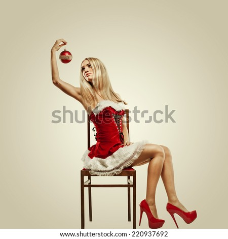 Beautiful woman in Santa Clause costume with Christmas gift. Winter portrait of sexy girl with copy space. Attractive new year and xmas party lady - stock photo
