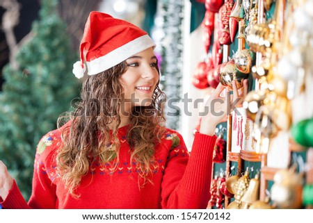 Beautiful woman in Santa hat buying Christmas ornaments at store - stock photo