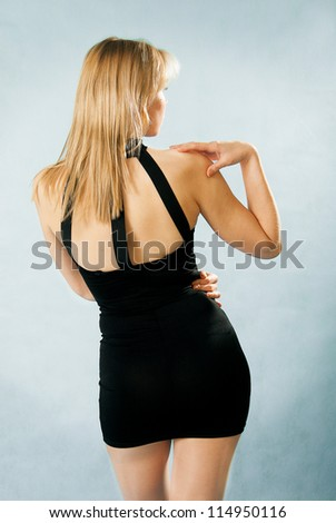 beautiful woman in sexy black dress standing with her back against blue background - stock photo