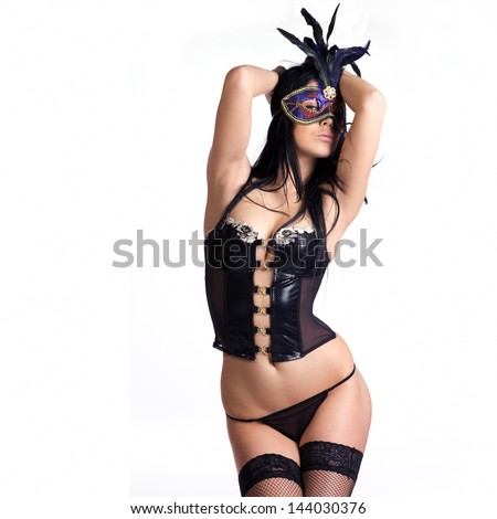 beautiful woman in sexy gothic or kinky black lingerie with a mysterious venetian facemask covering her face made in studio on a white background - stock photo