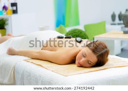 beautiful woman in spa salon during a stone therapy - stock photo