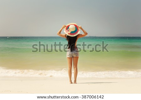 Beautiful woman in sun hat and bikini standing with arms raised to her head enjoying looking view of beach ocean on hot summer day. Beach vacation and travel - stock photo