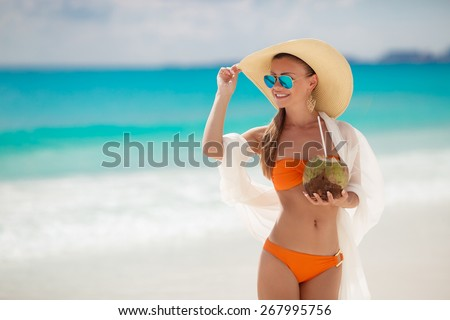 Beautiful woman in sunglasses and straw hat relaxing on a paradise beach with coconut. Happy young woman drinking coconut milk on beach. Young woman in pink swimsuit with coconut cocktail on the beach - stock photo
