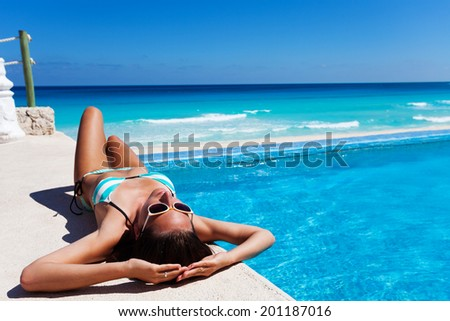 Beautiful woman in sunglasses sunbathes near pool - stock photo