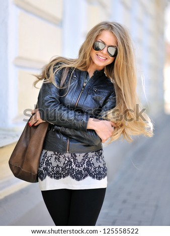Beautiful woman in sunglasses with handbag - stock photo