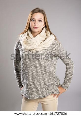 Beautiful woman in sweater is posing in studio, winter fashion - stock photo