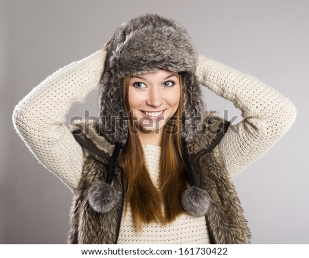 Beautiful woman in sweater is posing in studio, winter fashion