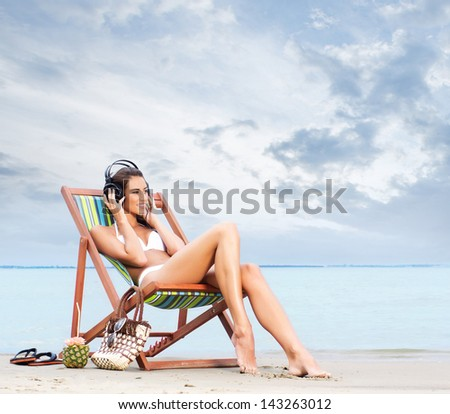 Beautiful woman in swimsuit relaxing on a beach - stock photo