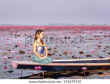 Beautiful woman in Thai traditional dress ,sitting in the boat. - stock photo