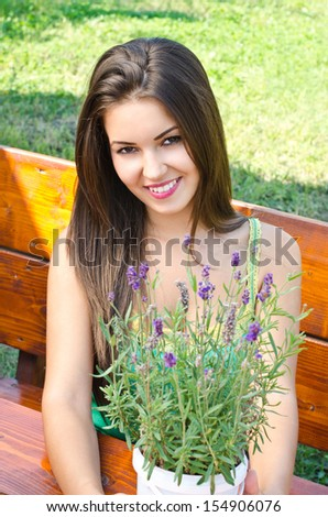 Beautiful woman in the garden sitting on a bench. Girl smiling holding a bouquet of lavender on a hot summer day.