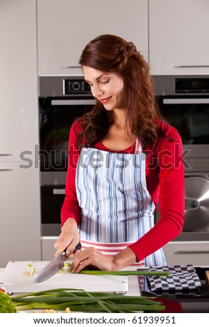 Beautiful woman in the kitchen preparing the vegetables for supper - stock photo